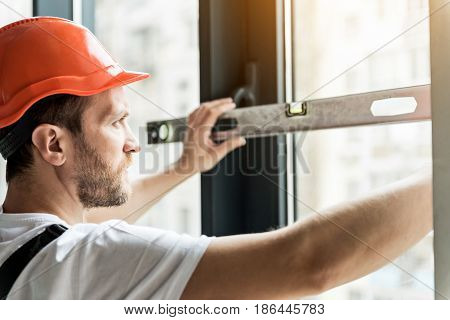 Serious constructor is using building level in order to check angle of deviation on window frame. He looking at instrument