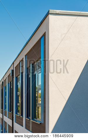 Corner detail of a modern white rendered building colourful blue and brown facade on a bright sunny day with clear sky. Abstract background.