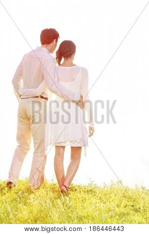 Rear view of couple standing arms around against clear sky
