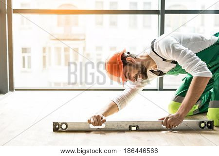Happy builder is bending down and putting building level on floor. He wearing work clothes