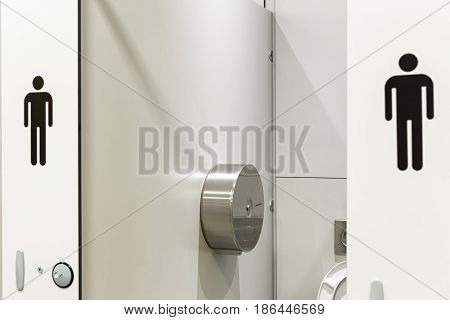 In an public building are Men's toilets with white doors and Male Symbol Decals