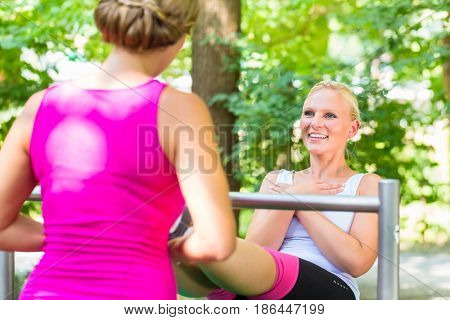 Pregnant woman and friend doing sports on workout bench