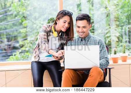 Two young dedicated Asian employees smiling while working together for finding solutions on a laptop in the office