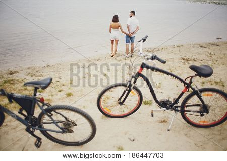 young sport couple walking by the river and uses communication rides a bike