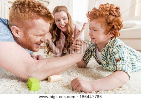 Side View Of Father And Son Playing Arm Wrestling With Mother Near By, Family Fun At Home Concept