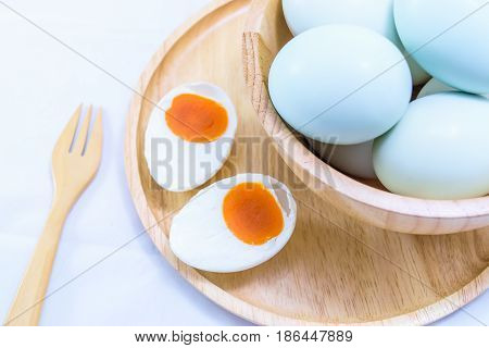 Salted duck egg in wooden cup isolated on white background.