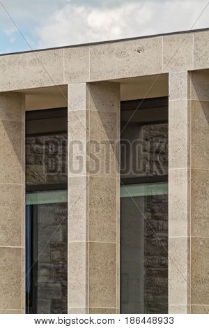 Building facade with elegant Birttish Portland Stone columns. The windows of the building reflecting the stones