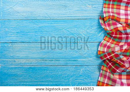 Red checkered tablecloth on a blue wooden table with copy space for your text. Top view.