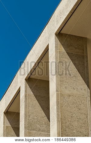 Building facade with elegant Birttish Portland Stone columns. Sunny day with blue clear sky.