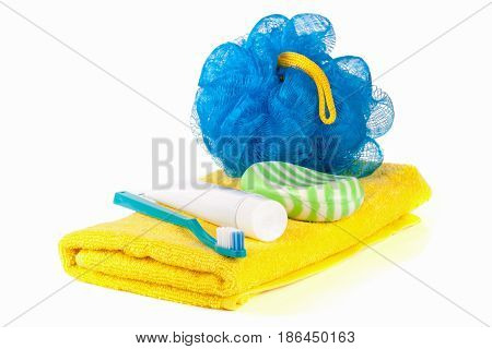 Hygiene products: soap with toothbrush and paste, loofah, towel isolated on white background.