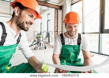 Joyful constructors are squatting and looking at drafts, they holding in hands. Men wearing work clothes