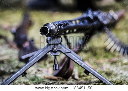 A rifle of machine gun with ammunition outdoor.