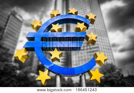 Euro sign at European Central Bank headquarters in Frankfurt Germany on abstract blurred background of dark dramatic clouds symbolizing a financial crisis