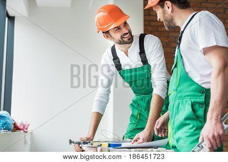Cheerful repairman is inclining on table and looking at his colleague with bright smile. They wearing work clothes