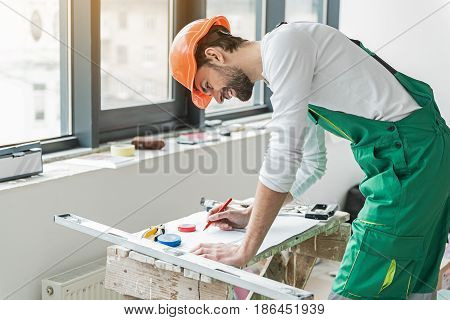 Busy cheerful repairman is inclining at desk with draft and amending it. He wearing orange helmet