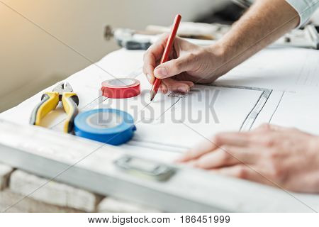 Repairman is using pencil in order to correct draft. Insulating tapes are near pliers at document. Focus on male hand holding pen. Close up