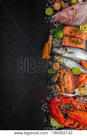 Whole lobster with seafood, crab, mussels, prawns, fish, salmon steak, mackerel and other shells served on black stone