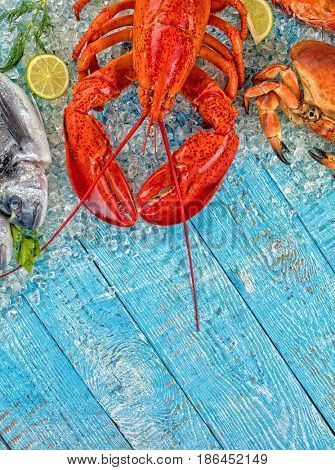 Whole lobster with seafood, crab, mussels, prawns, fish, salmon steak served on crushed ice and wooden table