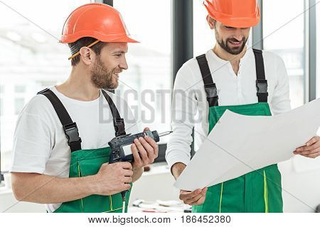 Happy repairman is holding drafts. His colleague keeping drill and looking at plan with smile. They wearing work clothes