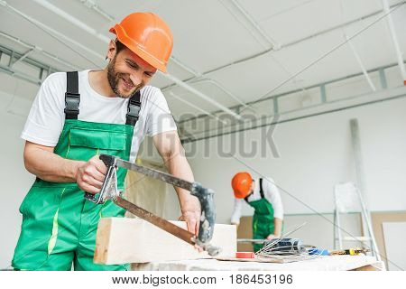 Hilarious repairman is using tool and looking at it with smile. His colleague inclining on table. They wearing work clothes. Low angle