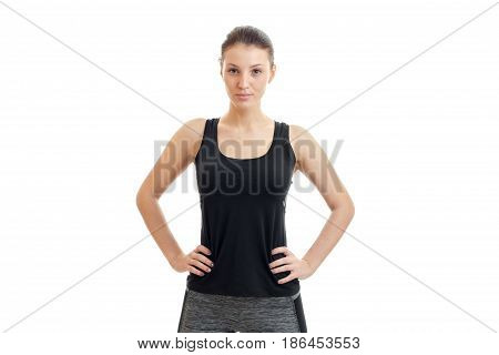 serious young brunette sport girl in black unform looking at the camera isolated on white background