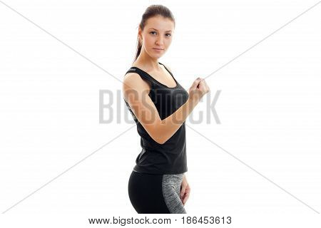 strong young brunette sport girl in black unform looking at the camera isolated on white background