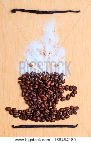 Cappuccino time. Roasted coffee beans placed in shape of cup with white froth vanilla pods on wooden surface background