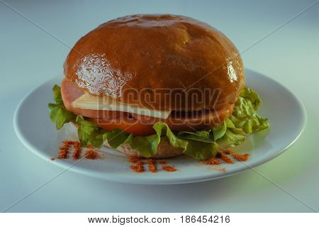 A large and tasty hamburger with sausage, cheese, tomatoes and a salad leaf on a white plate.