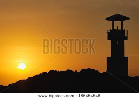 Photo of the night silhouette of the lighthouse in a bright orange sunset sky, Nang Thong Beach, Khao Lak, Thailand