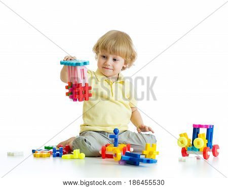 little child plays with construction set over white background