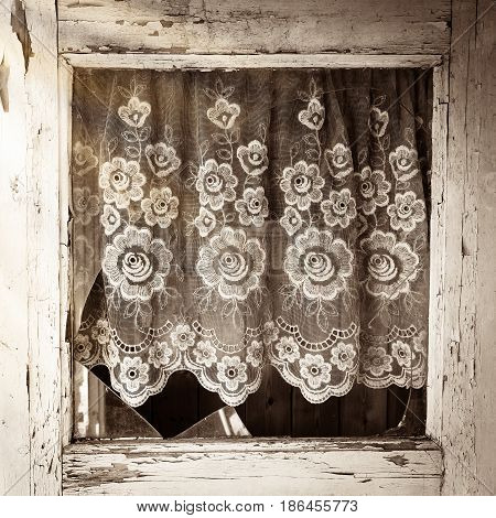 Close up of old house door window frame with broken glass and with white flower pattern curtain