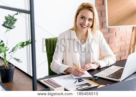 Beauty at work. Cheerful young beautiful woman looking at camera with happiness and making some notes in notebook. She is sitting at her working place