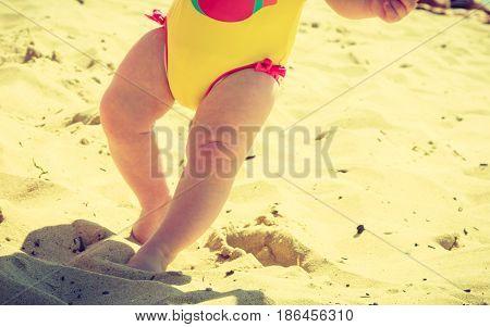Litte baby feet standing in sand walking on beach