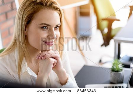 Feeling good. Portrait of cheerful young office worker keeping smile on her face. She is looking aside and touching her chin