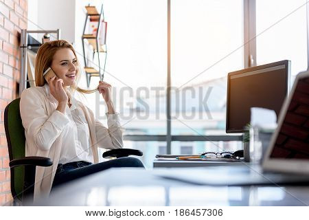 Distance communication. Cheerful young business woman talking by mobile phone. She touching hair while expressing positive emotions