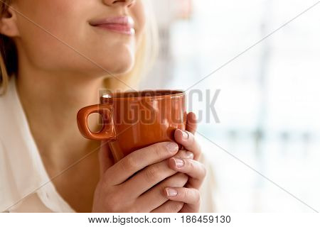 Making pause. Pleasant charming woman holding cup. She drinking coffee with pleasure while resting. Focus on mug