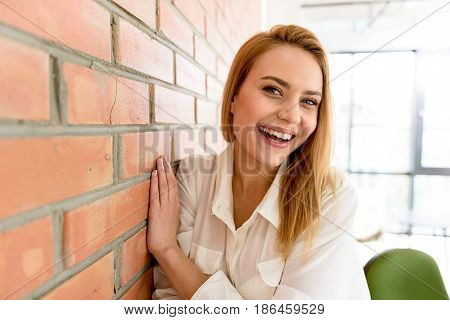 Involved in jubilation. Cheerful positive girl smiling and holding her hand on the wall. She looking at camera with gladness