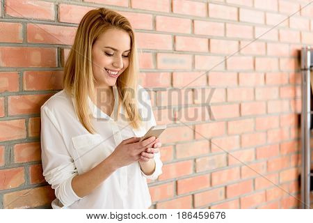 Always in touch. Waist-up portrait of laughing girl posing against brick wall while texting on smartphone. Copy space in the right side