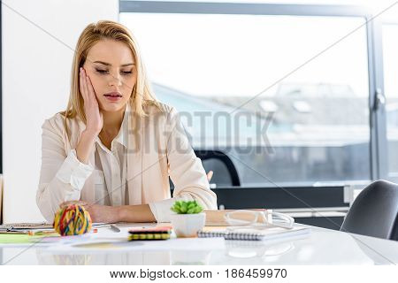 Need pause. Attractive blonde girl looking at her notes wearily. Copy space in the right side