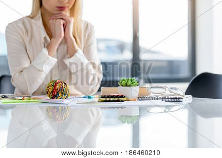 Wonderland. Reflection of different colored things in worktable. Elegant woman sitting at desk in background. Copy space in the right side