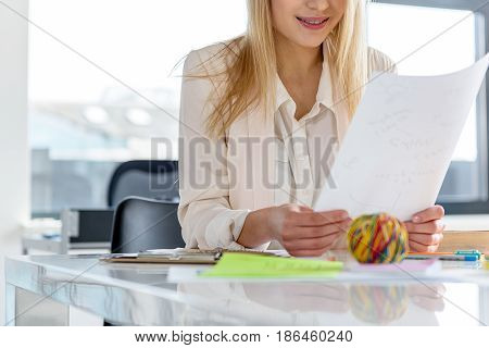 Good idea. Stylish smart girl holding piece of paper with smile. She is working against window.