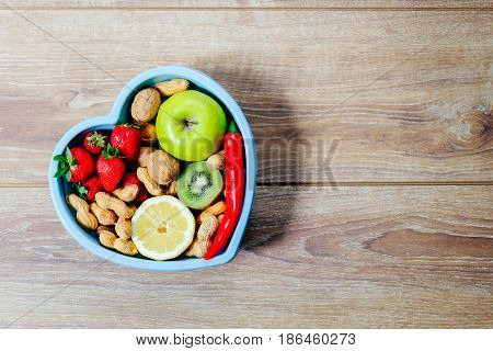 Heart Shaped Dish With Vegetables Isolated On Wooden Background