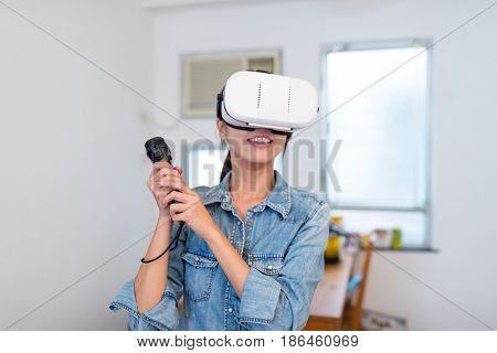 Woman playing game with virtual reality and joystick