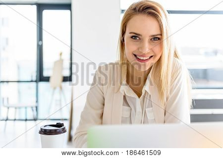 Confident business expert. Portrait of attractive young cheerful woman sitting in office. She looking at camera with smile