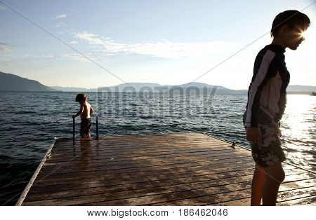 Caucasian boys standing on pier at lake