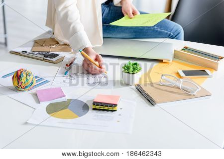 Searching of creative ideas. Close up of office table of successful businesswoman with different colored stationery on it. Girl sitting on desk while making some notes. Focus on her hand with pen