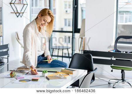 Much work. Cheerful energetic young businesswoman looking down with smile. She is making some notes while working with papers