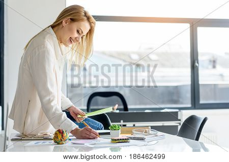 Ready to work. Joyful elegant businesswoman sitting on the table and holding papers while evincing positivity. She is holding sheet of paper and writing something in notepad