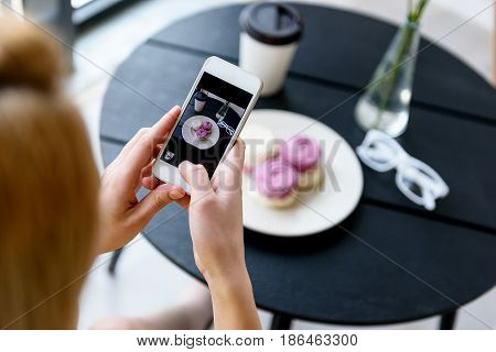 My sweet breakfast. Top view mobile phone photo of lady sitting at table. She making picture of her food