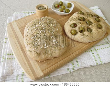 Focaccia bread with olives or rosemary on cutting board